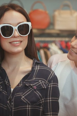 Beautiful woman smiling, trying on new sunglasses, shile shopping with her best friend. Two lovely young women enjoying shopping for eyewear together. Friendship, lifestyle concept