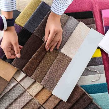 Young woman choosing among upholstery fabric samples, closeup. I
